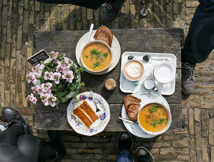 Overhead shot of a table with bowls of pumpkin soup coffee and a slice of cake. photo