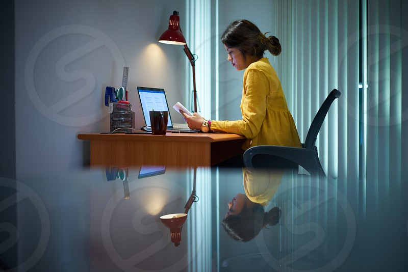 Young woman with laptop computer for homework. Tired hispanic girl and college education. Female student studying and using pc at home photo