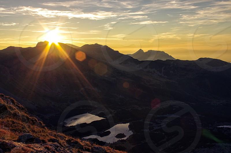 Lens flare through the mountain peaks. photo