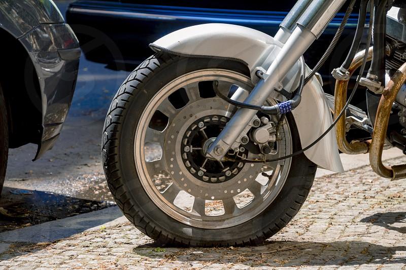 Security number padlock blocking motorcycle wheel on the street. photo