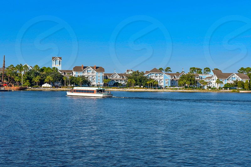 Orlando Florida. February 09 2019. Taxi boat sailing on lake with background of villas and lighthouse at Lake Buena Vista area (3) photo