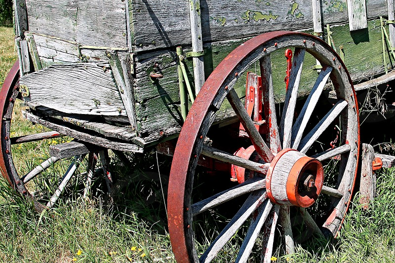 Detail of an old wooden rustic farm wagon with red wheels photo
