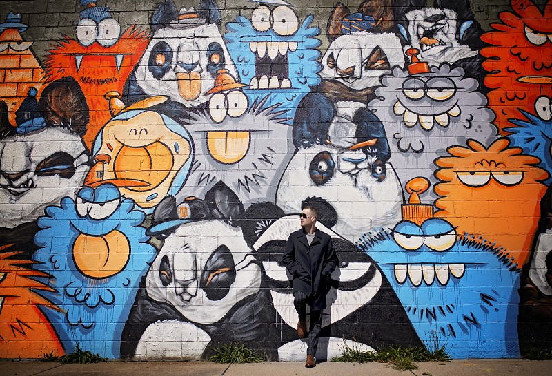 Male model posing in front of a graffiti mural  photo