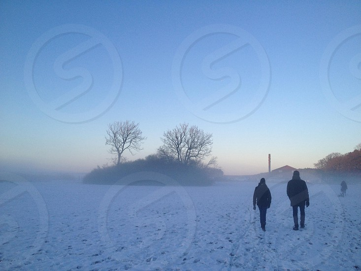 2 people standing on snow covered ground under blue sky photo