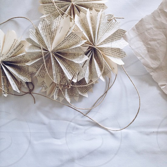 white folding paper near white coated wire on top of white paper photo