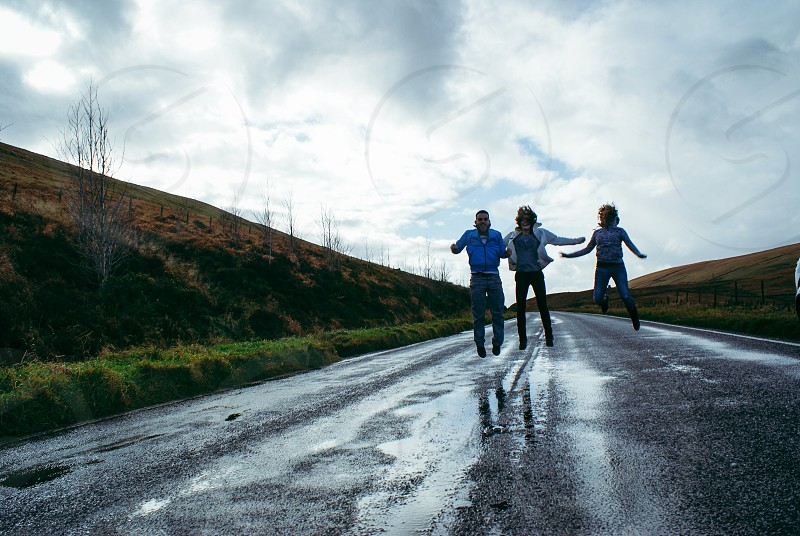 three people jumping on wet road photo