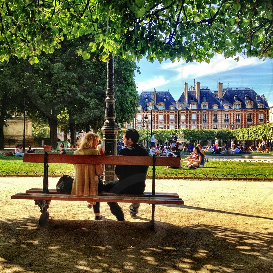 man and woman sitting on bench photo