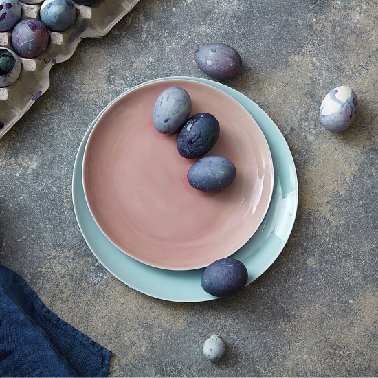 Easter blue eggs on a ceramic plate in a color of Living Coral Pantone on a gray marble background with textile towel place for text. Flat lay. Easter spring concept. photo