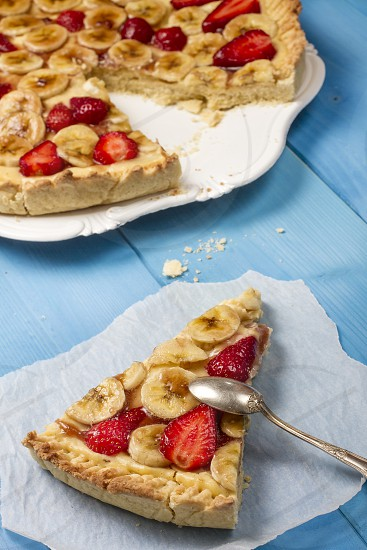 Bananas and Strawberries Tart on Grunge Wooden Table photo