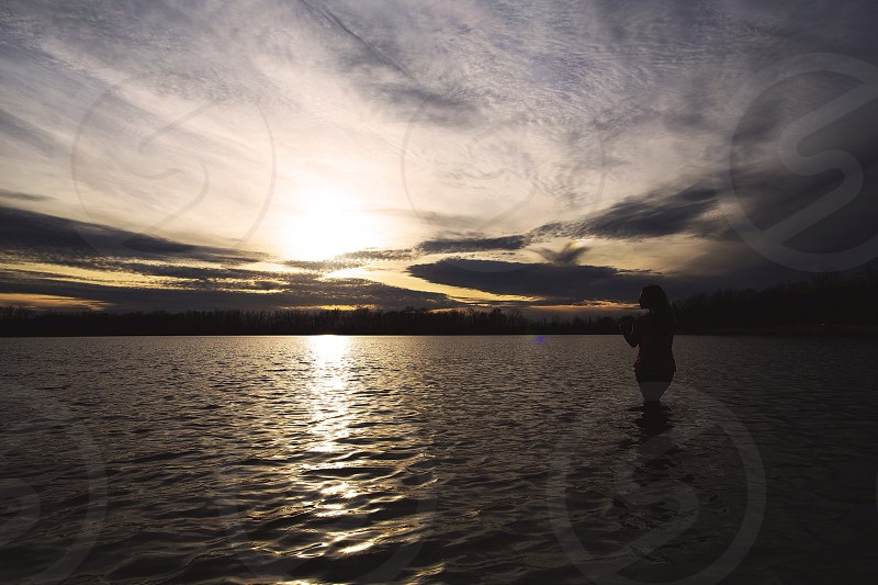 person standing in water during sunset photo