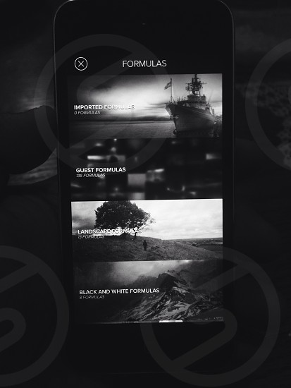black android smartphone showing ship tree and mountains on screen in black and white image photo