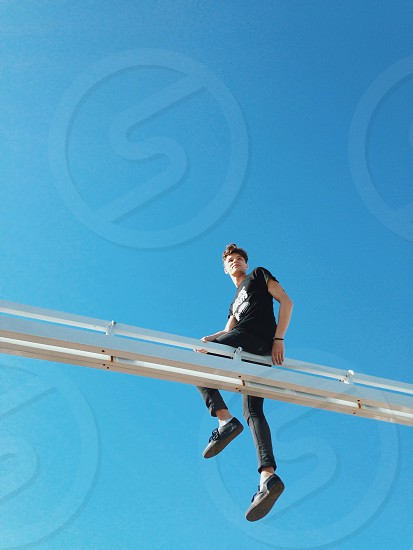 person in black t shirt sitting on white metal beam under blue sky photo