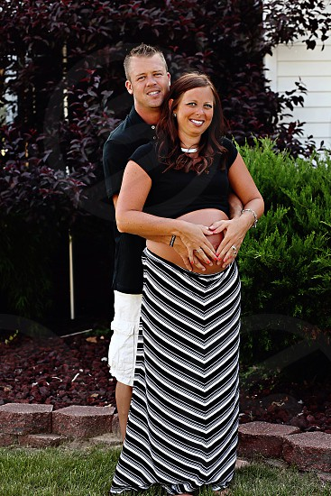 man with pregnant woman on lawn photo