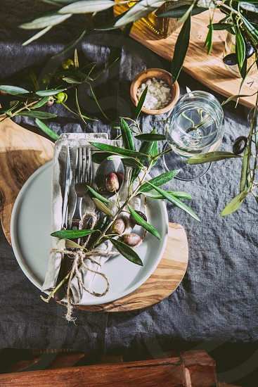 Table setting with gray Linen tablecloth and napkin white plate cutlery and and olive tree branch boards decoration. Top view. photo