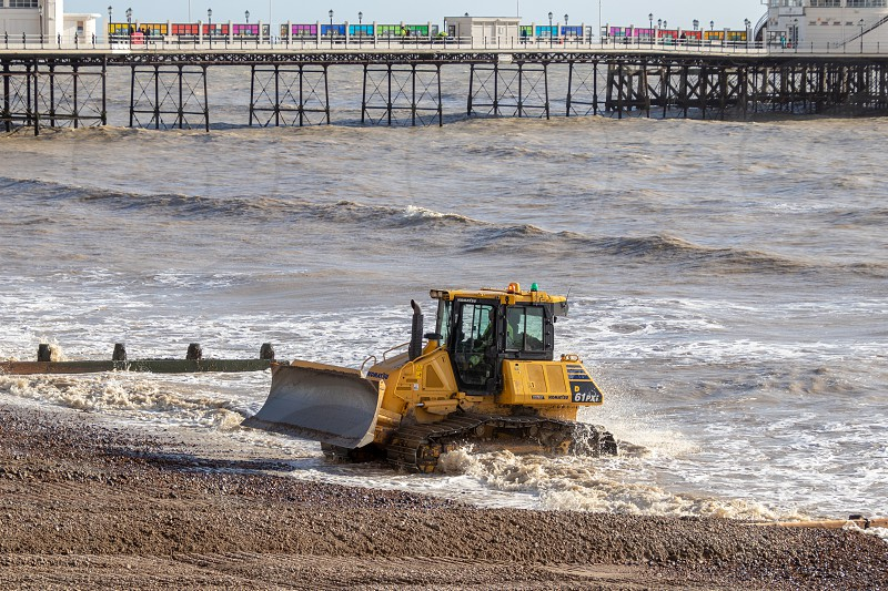 WORTHING WEST SUSSEX/UK - NOVEMBER 13 : Bulldozer repairing sea defences in Worthing West Sussex on November 13 2018. Unidentified people. photo