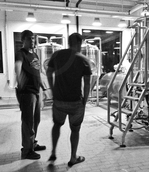 two male friends talking in a brewery setting photo