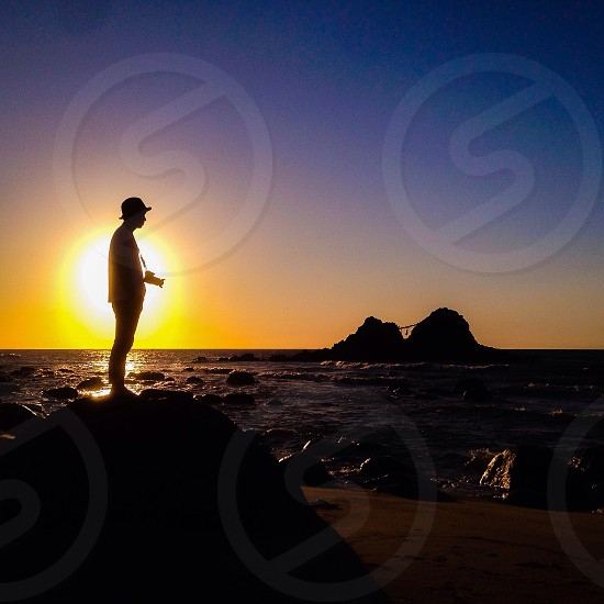 man standing on the rock through the sunset photo