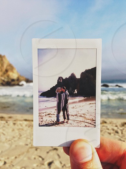 picture of person holding photo of couple kissing on beach photo