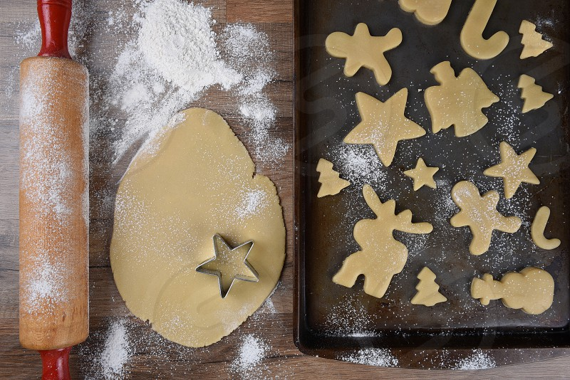 Top view of a baking sheet with a holiday shaped sugar cookies with raw dough and rolling pin on the side. photo