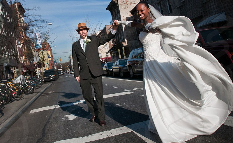 smiling bride in white holding hands with a groom in a suit and hat dancing on a city street photo