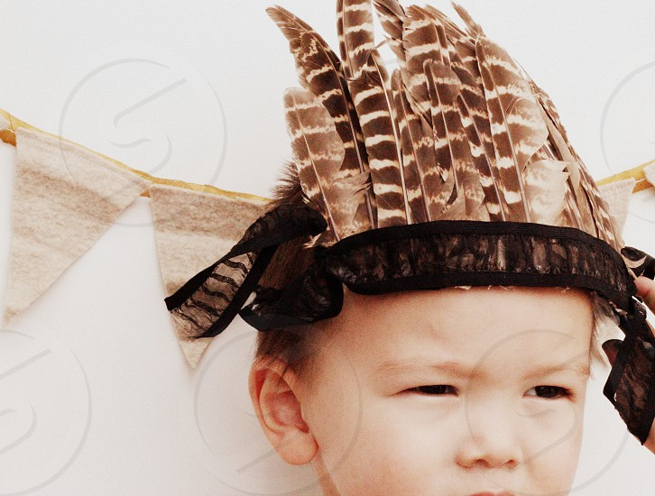boy day dreaming wonder discover play dress up dream feathers simple photo