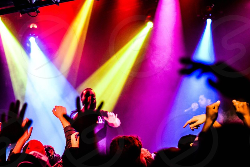 photo of man holding cordless microphone on stage with lights photo