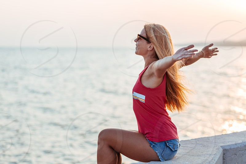 Young woman enjoying sunset by the sea photo