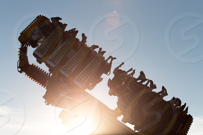Sun flare behind a ride at an amusement park photo