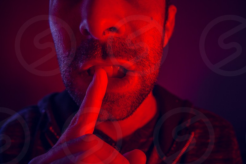Man with seductive facial expression holding finger on mouth. Close up portrait of flirty young man with shushing gesture with his finger to his lips looking at camera. photo
