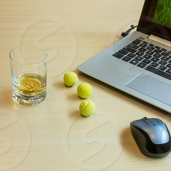 wimbledon is coming so some people might be tempted to follow the tennis on their laptop at work or even better at home with a glass of whisky and a few sweets looking tiny tennis balls. photo