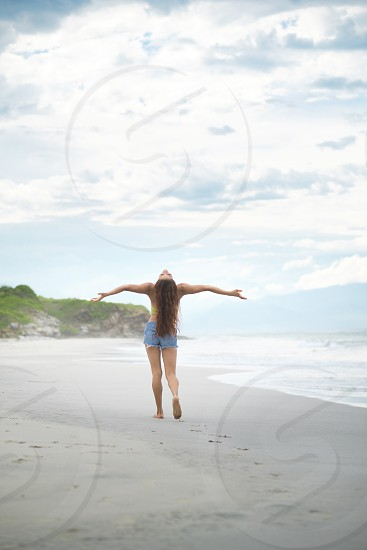 Woman raises arms and face in happiness toward the sky photo