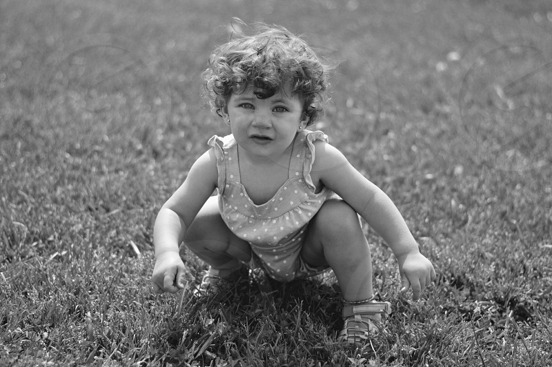 Baby walker squatting shoes anklet earrings grass dots romper eyes curls hair black and white b&w photo