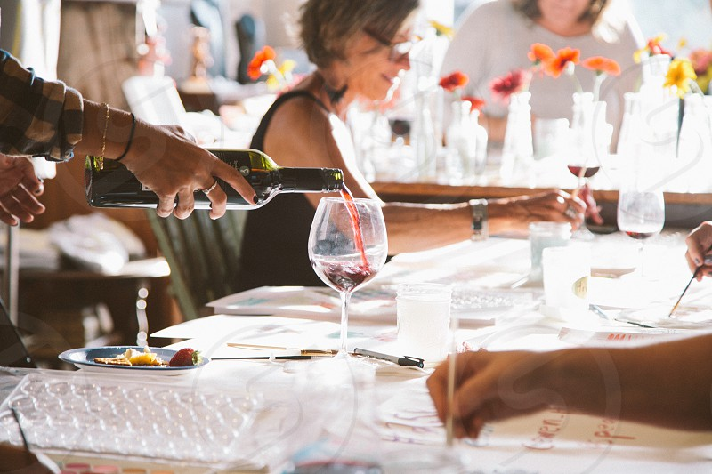 pouring wine into a glass on a table photo