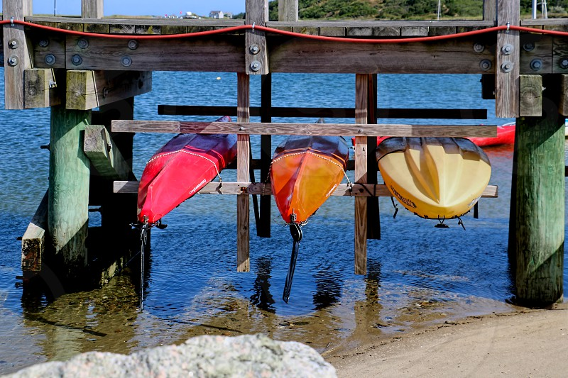 Colorful kayaks are lined up under a wooden dock or pier photo