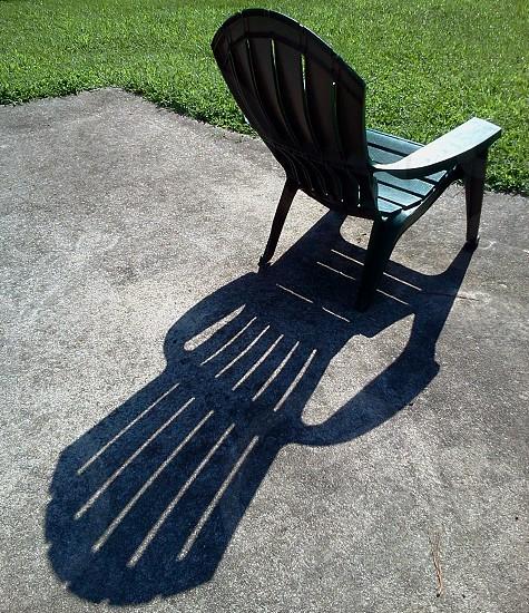 black monoblock chair on gray concrete pavement photo