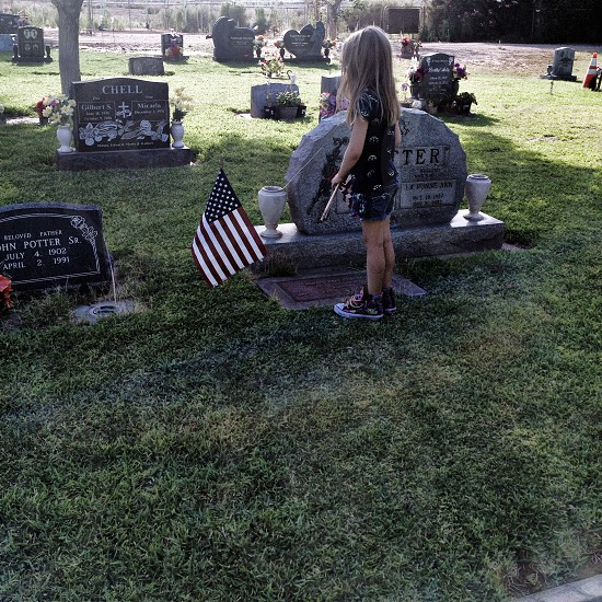 little girl standing at a grave with a flag photo