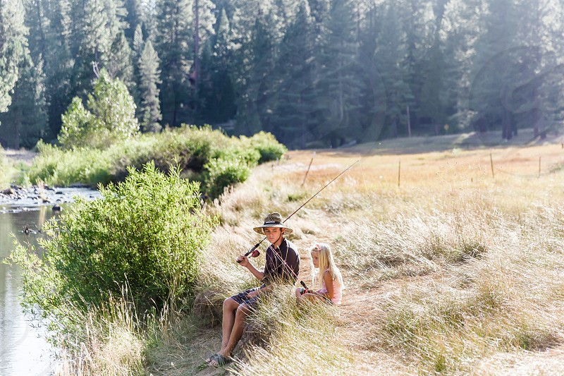 boy in a hat with a blonde girl holding fishing poles sitting along a river with pine trees in the distance photo