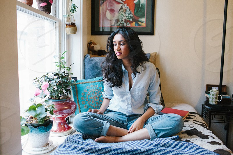 woman in blue long sleeved shirt and blue denim pants seated on bed photo