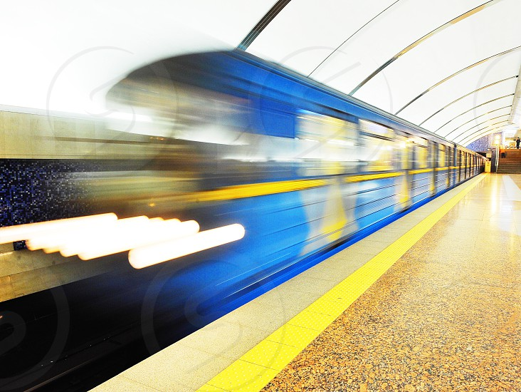 blue and yellow speeding train passing the subway station photo