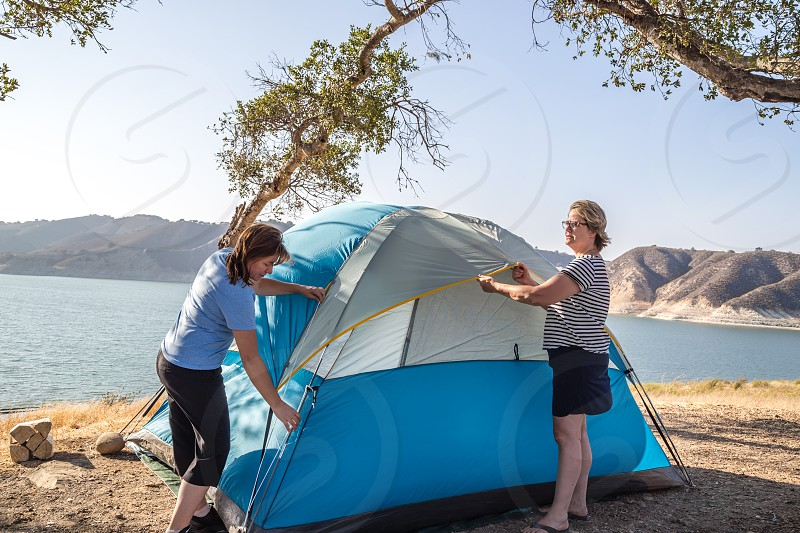 Two women setting up a tent photo