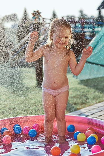 Little cute adorable girls enjoying a cool water sprayed by their father during hot summer day in backyard. Candid people real moments authentic situations photo