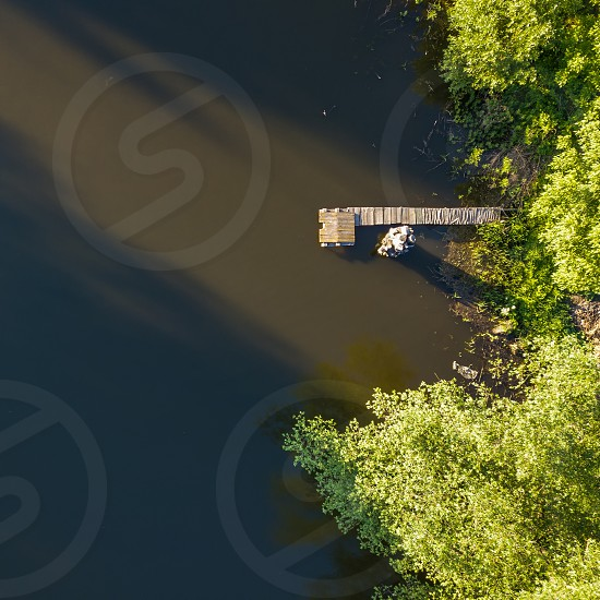 Aerial view over a sunny lake surrounded by pine tree forest and a wooden bridge. During the sunny summer day. Photo by drone photo