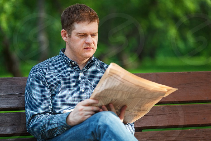 Man reads a newspaper on a bench in the park photo