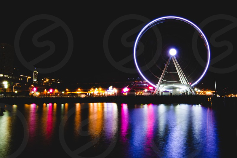 view of the ferris wheel and city at night photo