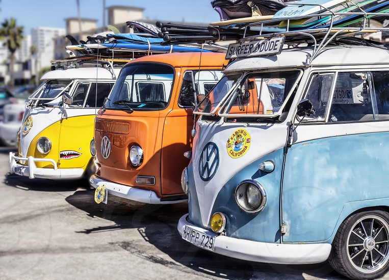 Colorful vintage VW busses with surfboards on top.  Beach summertime water sports surfing photo