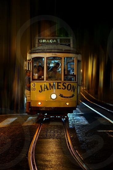 gray and yellow jameson graca 28 tram with hitched man wearing white and black stripe shirt and white cargo shorts photo