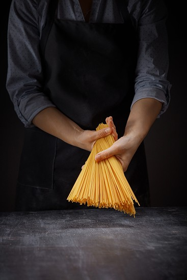 Process of making raw pasta in woman's hands over a wooden table on a black background photo