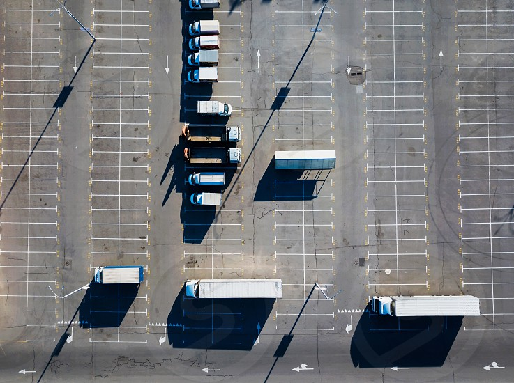Aerial view of a drone with different trucks in the parking lot with reflection of the shadows from street lamps on a sunny day. Top view photo