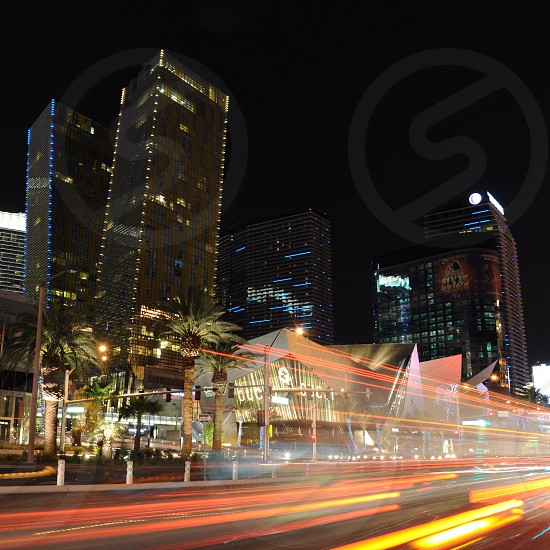 lights of cars speeding by city buildings at night photo
