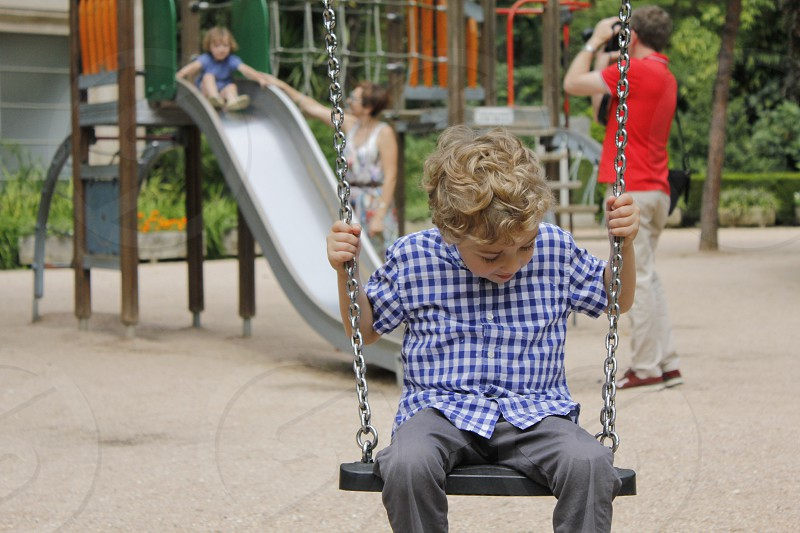 blonde kid on the park swing photo